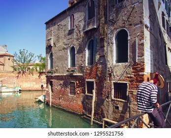 Venice, Ghetto: romantic landscape from the old Ghetto brige where a goldolier seats waiting and texting