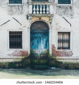 Venice Grand Canal (Canal Grande). Beautiful ancient architecture. Windows and blue  door on white wall. Door and wall with the mold.