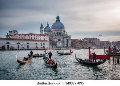 Venice, Italy - 01/04/2017: Gondolas with tourists in front of Basilica di Santa Maria della Salute