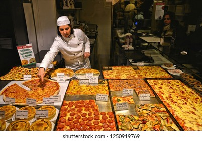 VENICE, ITALY 01.12.2018. Interior of pizzeria take away with woman show Different kinds of pizza on sale at the bakery in Venice, Italy