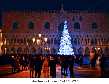 VENICE, ITALY 01.12.2018.  night view of the Christmas Tree with beautiful light in front of Doge's palace in San Marco Square full of people