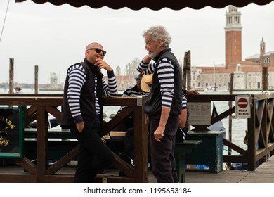 Venice / Italy - 04/16/2018: The fashionable Italian gondoliers in traditional costumes against the background of the island of San Giorgio, Venice.