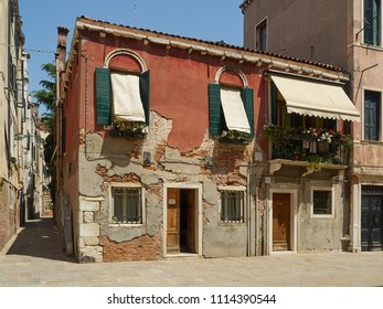 Venice, Italy - 06/05/2018: Colourful house in Venice, Italy with blinds and awning showing urban decay characteristic of the city with damaged plaster and brickwork on the walls