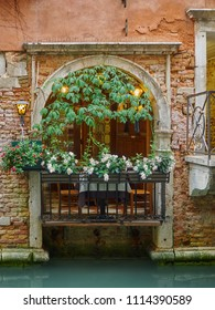 Venice, Italy - 06/05/2018: Old arched balcony with flowers in a wall with exposed brickwork on a canal, Venice, Italy, a popular tourist destination