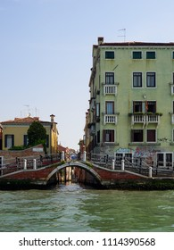 Venice, Italy - 06/05/2018: Old bridge with metal ramp over a canal, Venice, Veneto, Italy flanked by a colourful yellow house and palazzo, Unesco listed World Heritage Site