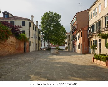 Venice, Italy - 06/05/2018: Open residential square with houses, ancient medieval well head and leafy green tree, Venice, Veneto, Italy