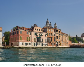 Venice, Italy - 06/05/2018: Palazzos or Venetian palaces on the Giudecca Canal, Venice, Italy with a restaurant deck viewed across the water