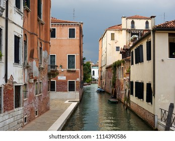 Venice, Italy - 06/05/2018: Quiet back canal with historic residential buildings and reflections on the water, Venice, Veneto, Italy