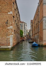Venice, Italy - 06/05/2018: Quiet back canal with moored boats and ancient brick architecture, Venice, Italy with a gondola in the distance