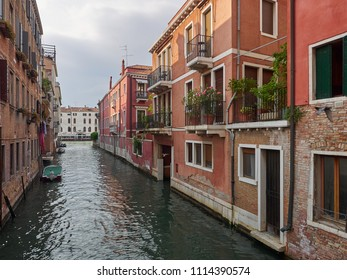 Venice, Italy - 06/05/2018: Tranquil back canal with colorful historic houses with balconies and greenery, Venice, Veneto, Italy , a popular tourist destination