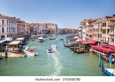 Venice, Italy, 07.04.2019: overview from Rialto Bridge to Grand Canal, boat taxi station and old houses along the canal.