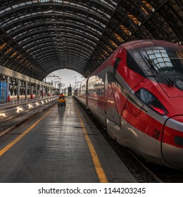 Venice, Italy - 08 May 2018: High-speed train Trenitalia at the train station of Milan. A worker is going along the platform on an electric vehicle. The platform has an openwork metal arch