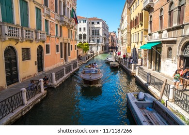 Venice, Italy - 15.08.2018: Boats on narrow canal between colorful historic houses in Venice.
