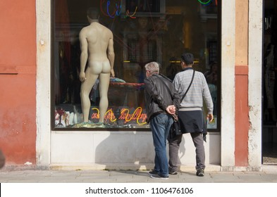 VENICE, ITALY - 16 MAY 2018:two men looking at  a sexy male mannequin in a Art Gallery