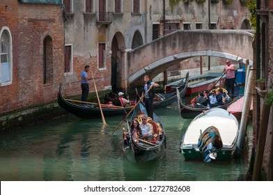 Venice, Italy - 18 06 2018. Canal crowded by gondolas ruled by gondoliers that carry tourists around. The gondola is the typical boat of Venice.