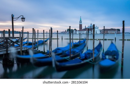 Venice, Italy - 20 May 2105: Gondolas moored on the lagoon, with the Church of San Giorgio Maggiore in the distance. Early morning light, showing the blurred boats rocking on the water