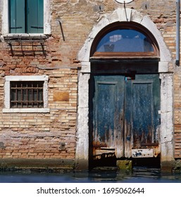 Venice, Italy, 2013: an old wooden door worn by time and water overlooks a canal in Venice