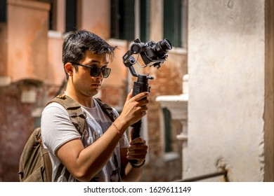 Venice Italy - 20th July 2019: A german photographer visiting the lagoon city, taking pictures of his colleague while filming with the new DJI Osmo gimbal.