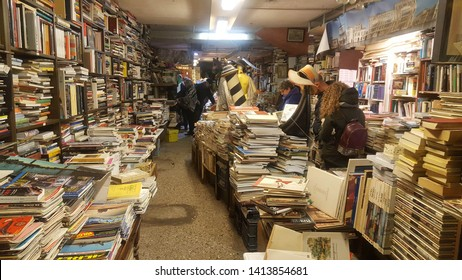 Venice, Italy - 20th November 2017: A unique book store in Venice were all the books are piled up in a haphazard fashion, some are evening in a gondola in the middle of the shop. Tourist must see.