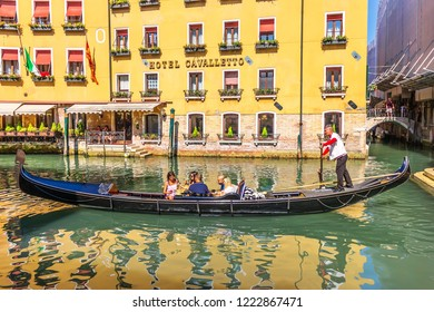 Venice, Italy - 22 August, 2018: A gondolier on a gondola with tourists in front of a fashionable hotel