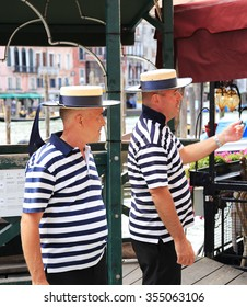 VENICE, ITALY - 26 JUNE, 2014: Gondoliers on the pier. The profession of gondolier is controlled by a guild, which issues a limited number of licenses