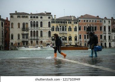 Venice, Italy - 29 October 2018:Tourists wearing rain wellies walk in the water during exceptional Acqua Alta - High Tide Floods. 70% of the lagoon city has been flooded by waters rising 149 cm