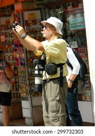 VENICE, ITALY - 6 JULY 2015 - Professional photographer, old man, hanging large lens around his neck,cameras with harness, and bag for lenses, cameras, tripods.6 July 2015 Venice