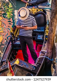 Venice, Italy - 6 June 2013: Portrait image of a gondolier with his head down concealed by a straw hat, using a smartphone whist standing on his gondola waiting for tourists