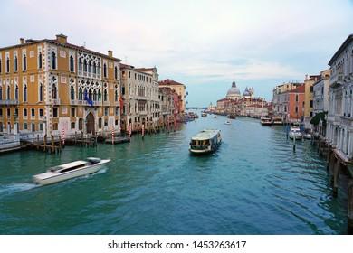 VENICE, ITALY -8 APR 2019- View of boats on the Grand Canal by the Palazzo Cavalli-Franchetti, near the Ponte dell'Accademia bridge in Venice.
