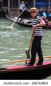 VENICE, ITALY - APR 14, 2013: Smiling young gondolier  in traditional dress on his gondola on the Grand Canal