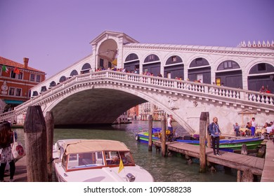 VENICE, ITALY - APR 16, 2018 - Gondolas and tourists mingle at the Rialto Bridge on the  Grand Canal of Venice, Italy