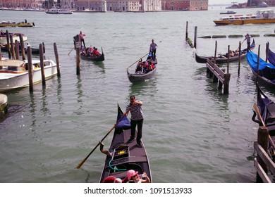 VENICE, ITALY - APR 16, 2018 - Gondolas approaching the quai near Piazza San Marco, Venice, Italy