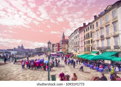 VENICE, ITALY - APR 16, 2018 - Tourists on the waterfront quai near the Doge's Palace, Venice, Italy