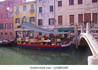 VENICE, ITALY - APR 16, 2018 - Vegetable boat delivers to small grocery store in Venice, Italy
