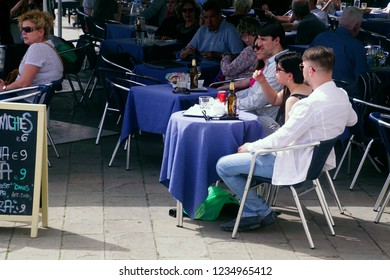 VENICE, ITALY - APR 16, 2018 - Tourists relax in a cafe on the Riva Schiavoni in Venice, Italy
