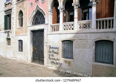 VENICE, ITALY - APR 16, 2018 - Antiwar graffiti and Door of parish church in medieval Venice, Italy
