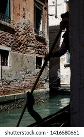 Venice, Italy - April 20, 2019: Gondolier standing in his gondola on the turquoise water of a Venetian canal holding a wooden paddle in his hand and turning around the corner of a red brick building