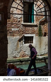 Venice, Italy - April 20, 2019: Gondolier standing in his gondola on the turquoise water of a Venetian canal holding a wooden paddle in his hand driving past red brick buildings