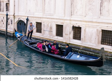Venice, Italy - April 20, 2019: Gondolier standing in his gondola holding a wooden paddle in his hand and transporting the tourists over the turquoise water of a Venetian canal past a white building