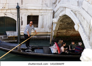 Venice, Italy - April 20, 2019: Gondolier in striped shirt with wooden paddle standing in his black gondola transporting tourists on the turquoise water of a Venetian canal underneath a bridge