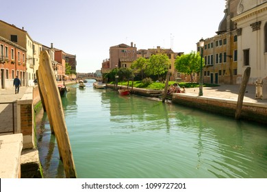 Venice, Italy, april 2018. Nice particoular view of the city, a wide canal and an interesting and uncommon spot where some trees ana a little meadow give shadow to the local people