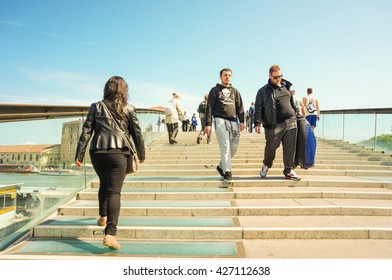 VENICE, ITALY - APRIL 22, 2016: People walking on a large canal bridge on the city center on a very sunny day