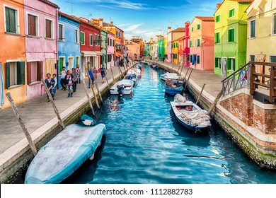 VENICE, ITALY - APRIL 30: Colourful houses along the canal on the island of Burano, Venice, Italy, April 30, 2018. The island is a popular attraction for tourists due to its picturesque architecture