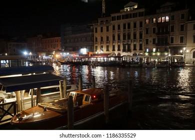 VENICE, ITALY - AUG 10, 2018 - Gondola in small canal at night in Venice, Italy