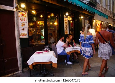 VENICE, ITALY - AUG 10, 2018 - Tourists dine at outdoor restaurant in Venice, Italy