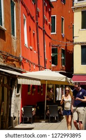 VENICE, ITALY - AUG 10, 2018 - Tourists walk the narrrow streets with bright colored buildings of  Venice, Italy