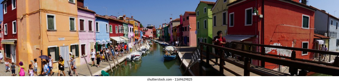 VENICE, ITALY - AUG 11, 2018 - Panorama of tourists on a canal with brightly painted houses in Burano Island, Venice, Italy