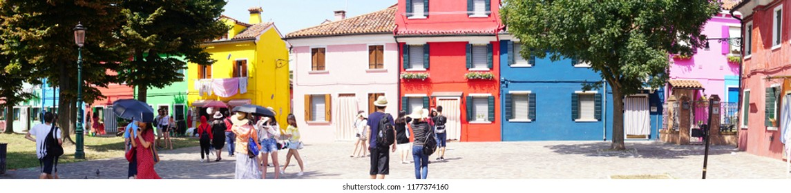 VENICE, ITALY - AUG 11, 2018 - Panorama of tourists and brightly painted houses on the island of Burano, Venice, Italy
