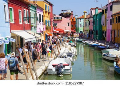 VENICE, ITALY - AUG 11, 2018 - Tourists on a canal with brightly painted houses in Burano Island, Venice, Italy