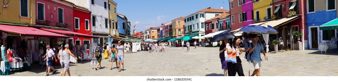 VENICE, ITALY - AUG 11, 2018 - Panorama of tourists and brightly painted houses in Burano Island, Venice, Italy
